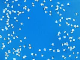 Scattered white snowflakes on a blue background. Simple flat lay with copy space. Stock photo. photo