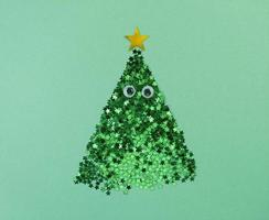 Christmas tree shape from confetti stars with eyes on a green paper. photo