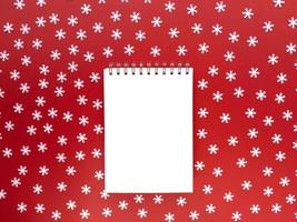 Blank sheet of notebook with scattered white snowflakes on red background. Educational concept. Simple flat lay with copy space. Stock photo. photo