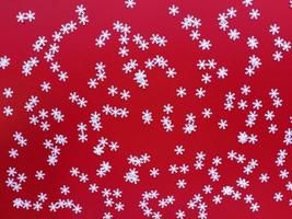 Scattered white snowflakes on red background. Simple festive flat lay. Stock photo. photo