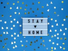 caja de luz con cotización en casa sobre un fondo azul con confeti. cuarentena navideña. foto