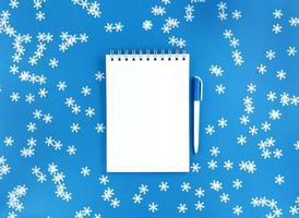 White blank sheet of notebook and a pen on a blue background with scattered confetti snowflakes. Holiday education concept. Stock photo. photo