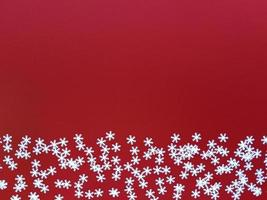 copos de nieve blancos dispersos sobre fondo rojo. plano simple con espacio de copia. foto de stock.