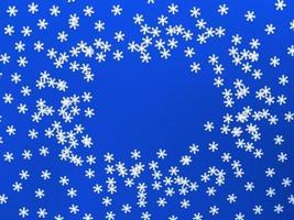 copos de nieve blancos dispersos sobre fondo azul. plano simple con espacio de copia. foto de stock.