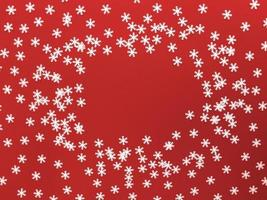 Scattered white snowflakes on red background. Simple flat lay with copy space. Stock photo. photo