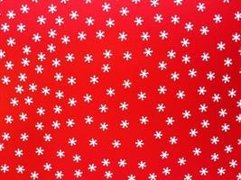 copos de nieve blancos dispersos sobre fondo rojo. plano festivo simple. foto de stock.