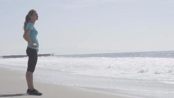 A woman runner resting on the beach after her run. video