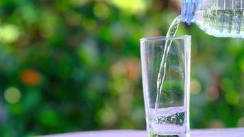 versando acqua potabile sul tavolo e concetto di assistenza sanitaria con acqua minerale video