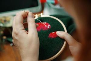 Embroidery process with cotton thread of mushrooms hat. photo