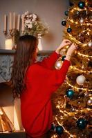 Asian woman decorating Christmas tree. photo