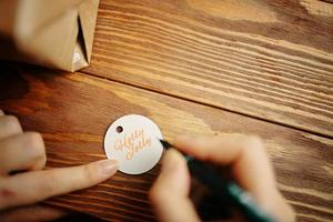 Las manos de las mujeres con lápiz escriben inscripción en la etiqueta de regalo foto