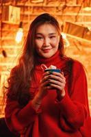 Asian girl with mug of hot chocolate. photo