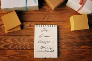 Top view of spiral notebook and gift boxes on wood table background. photo