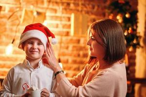 Mother puts Santa Claus Christmas hat on her child photo