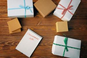 Wooden table with gift boxes and notepad with list of Christmas gifts. photo