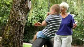 Senior woman spinning young boy on swing video