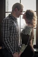 A young couple in a romantic relationship look at each other in the background of the window. Marriage proposal. photo