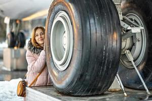 A young woman looks out from behind large wheels. The front landing gear of a passenger plane being repaired at the airport photo