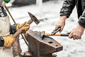 A blacksmith man and his son forge a horseshoe on an anvil. photo