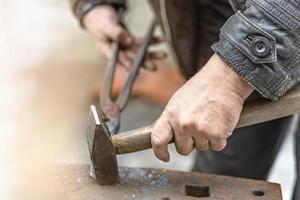 A blacksmith man forge a horseshoe on an anvil photo