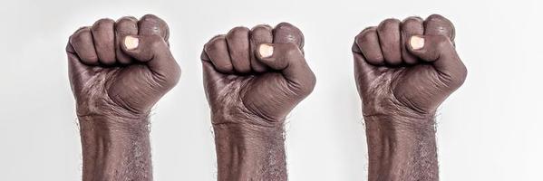 manos masculinas apretadas en un puño sobre un fondo blanco. un símbolo de la lucha por los derechos de los negros en américa. protesta contra el racismo. foto