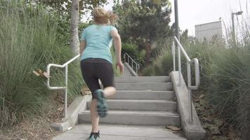 A woman runner running stairs. video