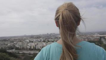 A young woman runner standing at the top of trail overlooking neighborhood. video