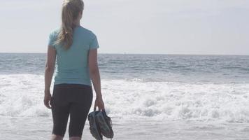 en kvinnalöpare som vilar på stranden efter hennes körning. video