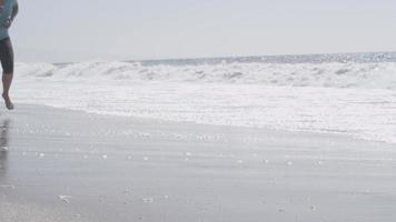 A woman runner going for a run on the beach. video
