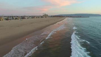 Luftaufnahme eines jungen Mannes, der am Strand läuft. video