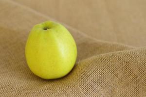 Manzana verde cruda sobre fondo de arpillera foto