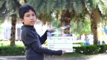 Asian boy holding movie slate colors board for movie cinema and television industry video