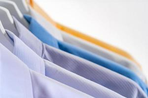 Men's dress shirts, Clothes on hangers on white background photo