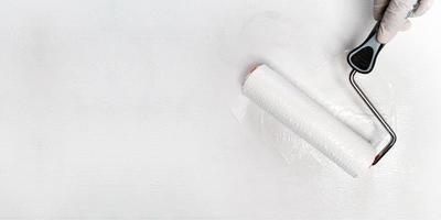 Pintura a mano con pintura de color blanco con rodillo de pintura foto