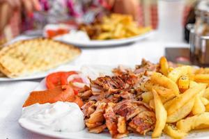 Gyros griegos en un plato con patatas fritas y verduras foto