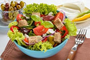 Fresh vitaminic green salad with bread cubes and tasty selection of vegetables. photo
