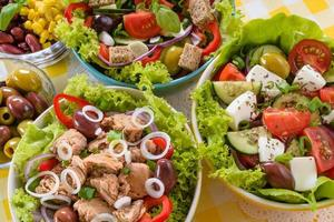 Tuna, Vitaminic green and Greek salad with feta and tasty selection of vegetables. photo