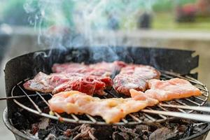 Grilled meat, pork, beef and chicken meat on barbecue, grill. Shallow depth of field. photo