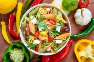 ensalada de pasta con tomate, rúcula, pepino, pimientos, pimientos picantes, aceitunas negras y verdes y queso feta. vista superior. foto