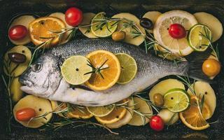Dorada en la bandeja de horno listo para hornear con patatas, romero, limón, naranja, aceitunas, tomates, cebolla y lima. orata fresca, preparación de pescado dorade foto