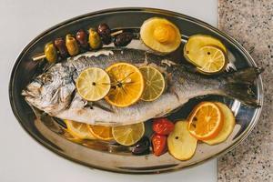 dorada pescado al plato al horno con patatas, romero, limón, naranja, aceitunas, tomates y lima. orata fresca, preparación de pescado dorade. foto