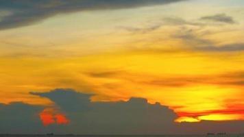 Blur sunset red yellow orange cloud on the sky over sea with finsing boat and cargo ship time lapse video