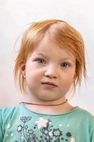 retrato de una pequeña niña sonriente con el pelo rojo foto