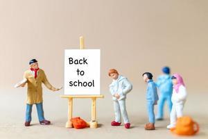 Maestros y estudiantes cerca del lienzo en el caballete con la palabra regreso a la escuela. foto