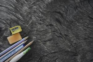Concepto de regreso a la escuela y la educación en la pizarra de madera vieja en la vista superior con espacio de copia con bolígrafos, lápiz y borrador foto
