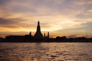 Silhouette of Wat Arun Temple at sunset on Chao Phraya river landmark of Bangkok Thailand photo