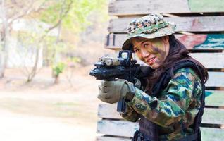 Retrato mujer soldado disparando con rifle ametralladora maniobra en el bosque foto