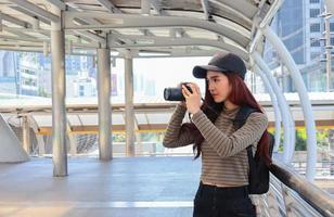 Portrait of young Asian tourist holding a camera Happy life concept photo
