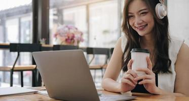 Young Asian businesswoman, beautiful charming smiling holding a cup in the office photo