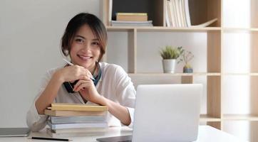 Sonriente mujer asiática que trabaja en el escritorio con libros y computadora portátil foto